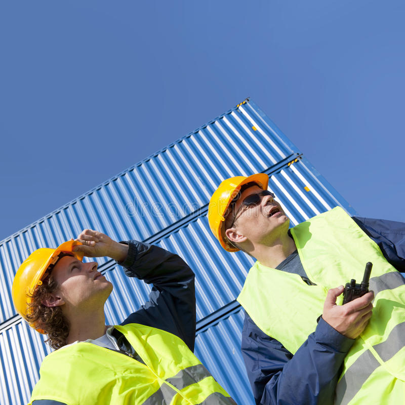 Dockers at work. Two dockers, wearing a hard hat and safety vests at work under a blue sky, with huge containers in the background stock photos