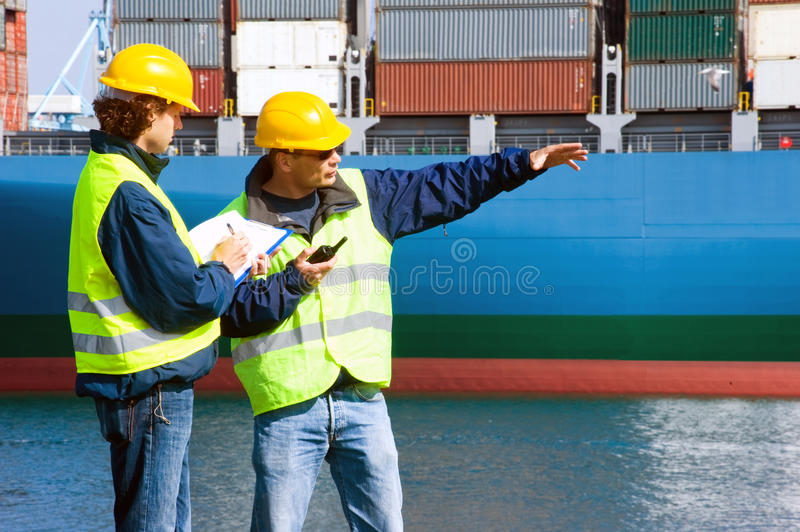 Dockers at work. Two Dockers at work in an industrial harbor, giving instructions, and writing them down royalty free stock images