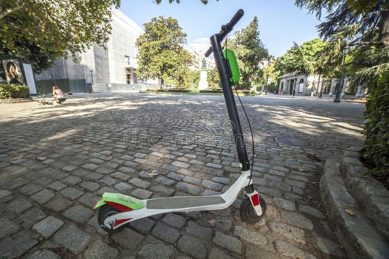 Dockless electric kick scooters from a scooter-sharing system parked on a sidewalk. One vehicule for rent at Madrid old town stock photos