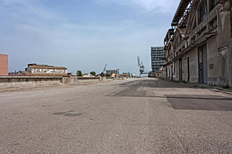 Docks. Desolated street on the docks of port - desert suburbs of the city with abandoned warehouses and factories stock image