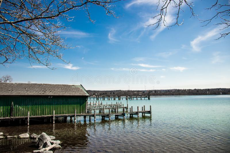 Docks at the lake in Starnberg, Germany. Several docks at the lake in Starnberg Germany with a clear blue sky and cloud backgrounds with tree branches for spring royalty free stock image