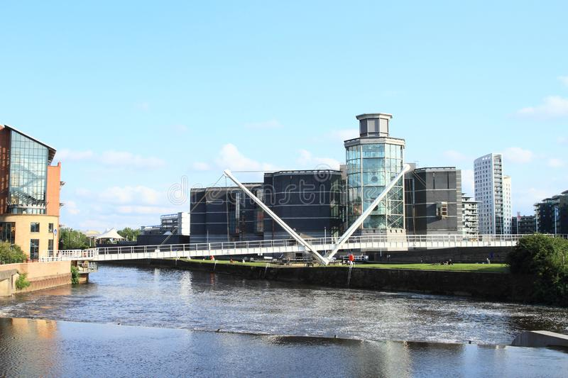 Docks of Leeds. River with weir and white hanging bridge in docks with Royal Armouries Museum behind in Leeds in Great Britain. River traveling concept stock image