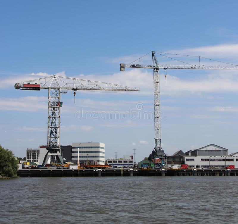 Docks with ships and cranes along the riverside of the river Lek or Noord in the Netherlands. royalty free stock photography