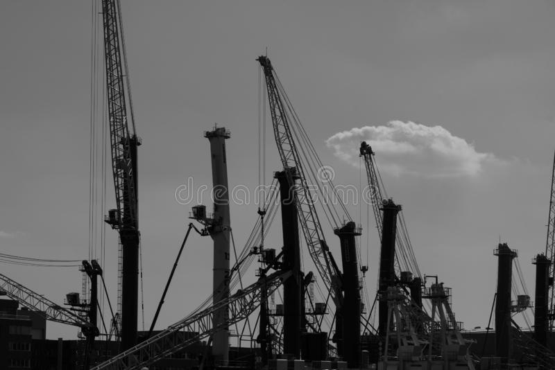 Monochrome silhouttes of dockside cranes at the industrial harbour in Rostock. Monochrome details of dockside cranes at the europort harbour in Rostock stock photo