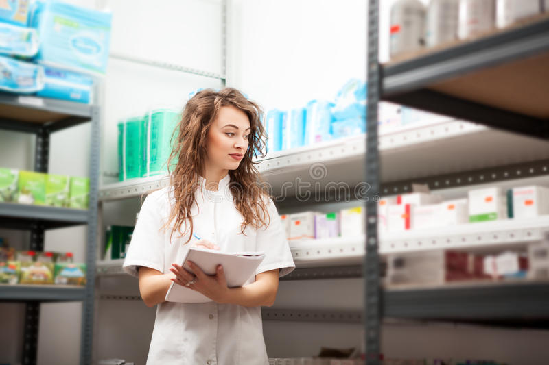 Docor in storage writting down the number of drugs and pills royalty free stock image