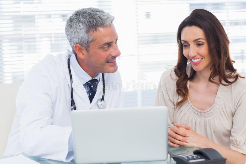 Docter pokazuje coś na laptopie jego pacjent zdjęcie royalty free