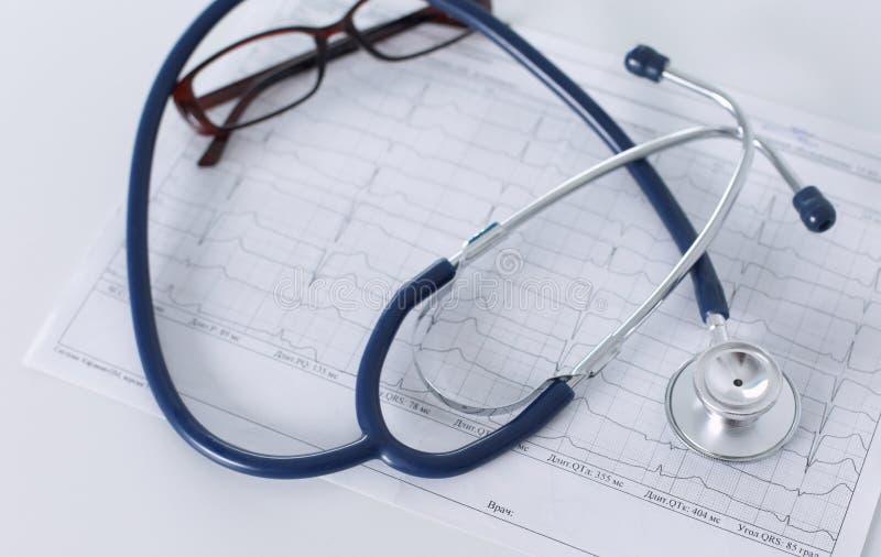Docterwerkplaats met een grafiek van het stethoscoopcardiogram met medische lijstclose-up, voor hartverslag stock foto's