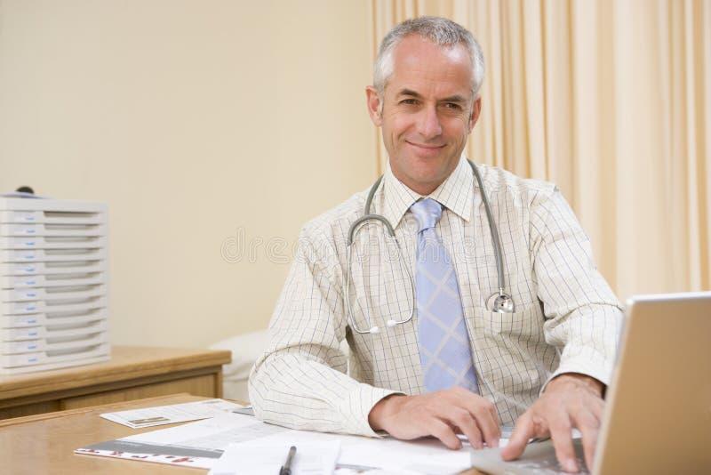 Docteur à l'aide de l'ordinateur portatif dans le bureau du docteur photographie stock libre de droits