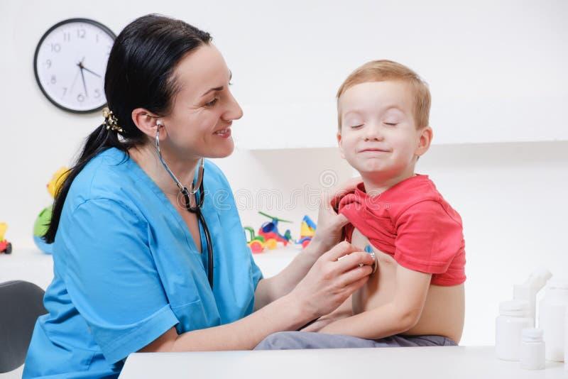 Docteur à l'aide du stéthoscope à examiner le petit garçon doux photo stock