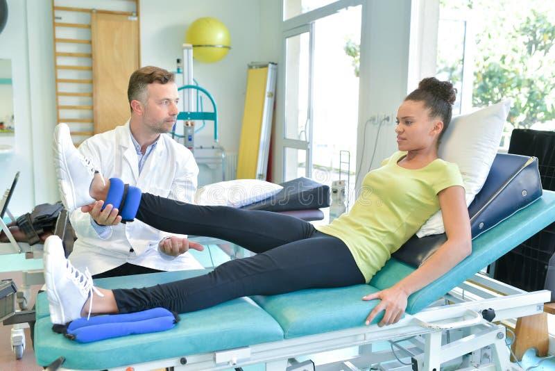 Docteur étirant la jambe de femme sur la session de physiothérapie image libre de droits