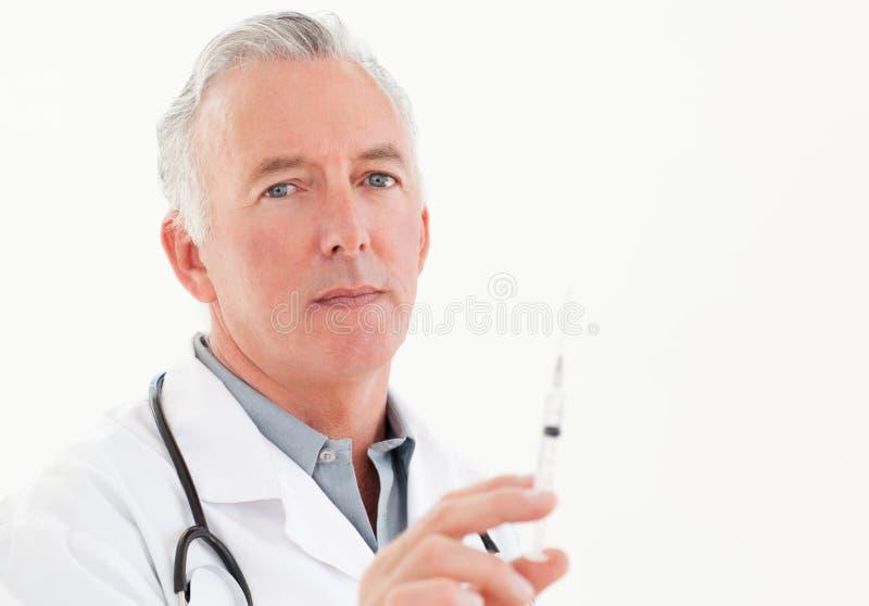 Docteur aîné avec des seringues photo stock