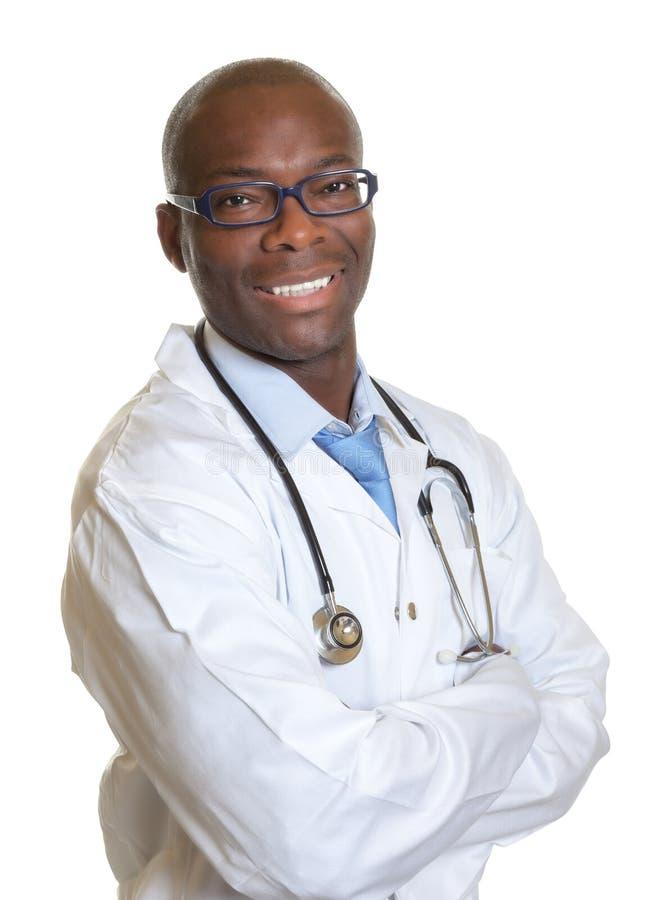 Docteur africain riant avec les bras croisés photo libre de droits