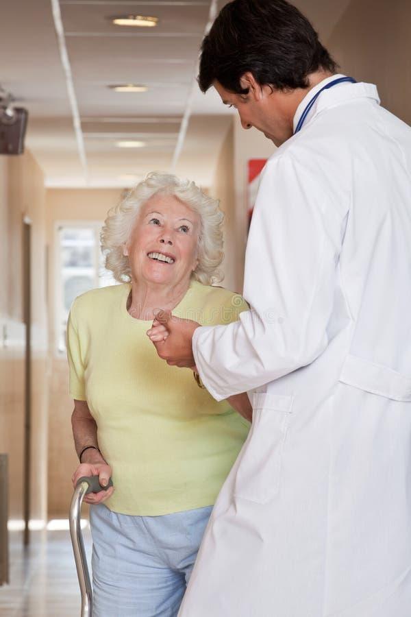 Docteur aidant le bâton de marche patient d'utilisation photo libre de droits