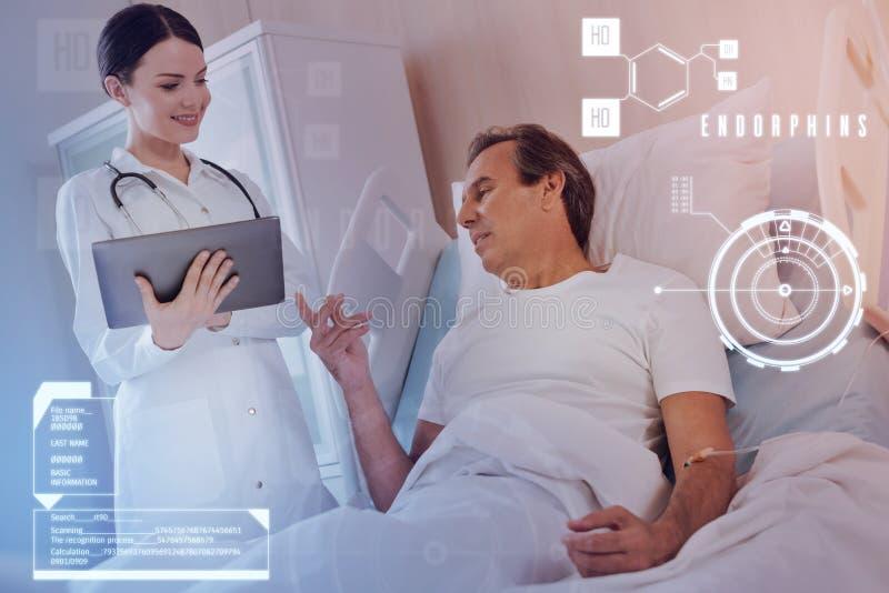 Docteur aimable souriant tandis qu'un patient curieux posant des questions photographie stock