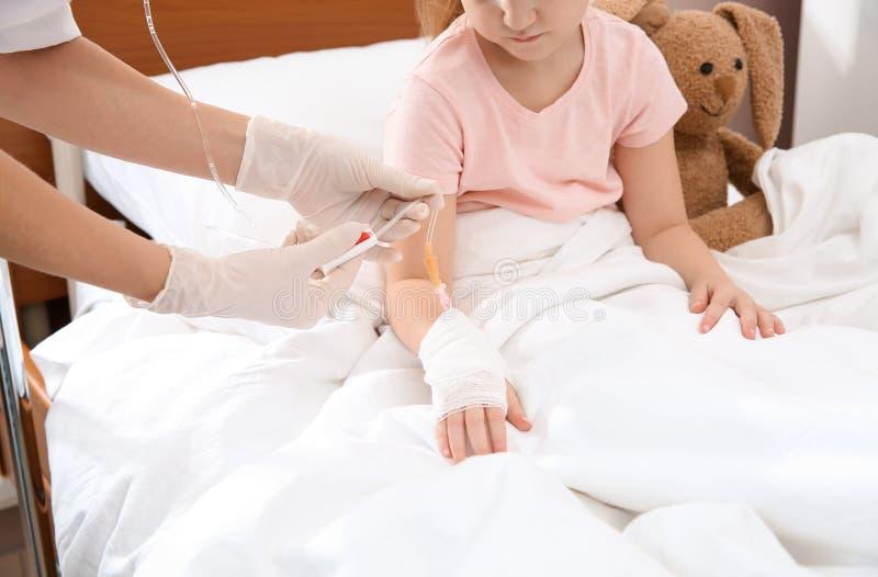 Docteur ajustant l'égouttement intraveineux à peu d'enfant photo libre de droits