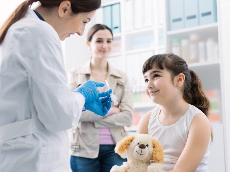 Docteur amical montrant une seringue à une fille avant de donner l'injection photos libres de droits