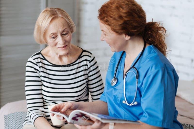 Docteur animé aimable discutant quelque chose avec son patient photo libre de droits