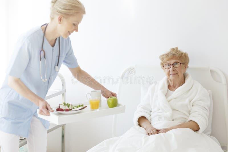 Docteur apportant la nourriture à l'aîné images stock