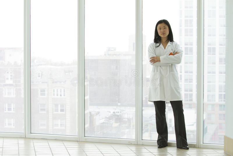 Docteur asiatique féminin se tenant avec des bras croisés images stock