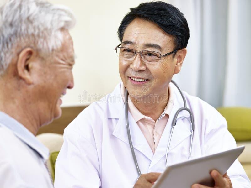 Docteur asiatique parlant au patient photo libre de droits
