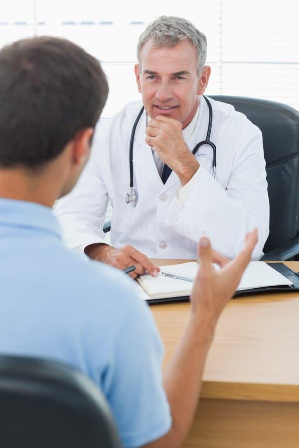 Docteur attentif écoutant son patient photo stock