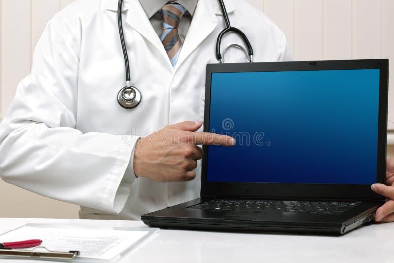 Docteur avec l'écran blanc d'ordinateur portatif photos stock