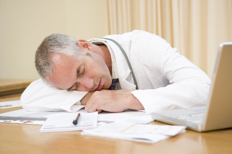 Docteur avec l'ordinateur portatif dormant dans le bureau du docteur image stock