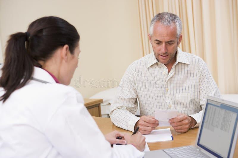 Docteur avec l'ordinateur portatif et l'homme dans le bureau du docteur photo libre de droits