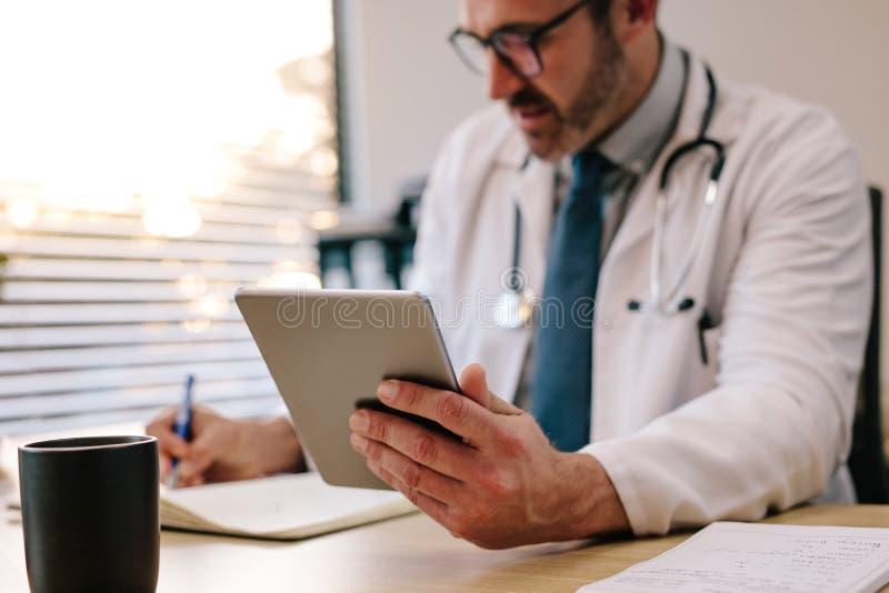 Docteur avec le comprimé numérique écrivant des notes à son bureau image stock