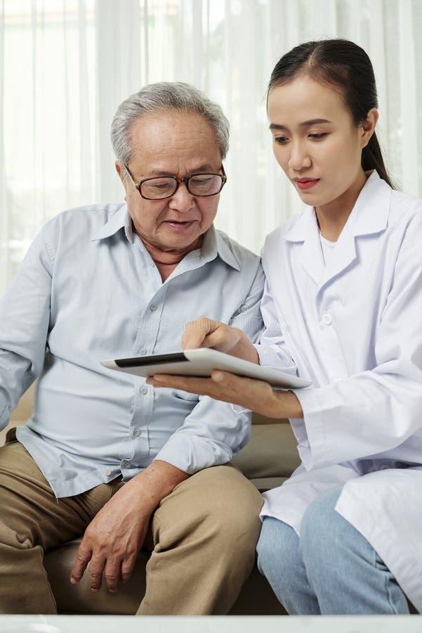 Docteur avec le patient à l'aide du PC de comprimé photographie stock