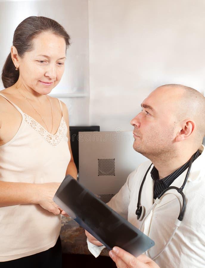 Docteur avec le rayon X de regard patient image libre de droits