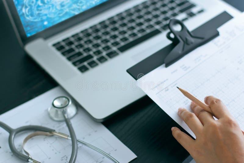 Docteur avec le stéthoscope sur le diagramme de rapport, fonctionnant avec le labtop image stock
