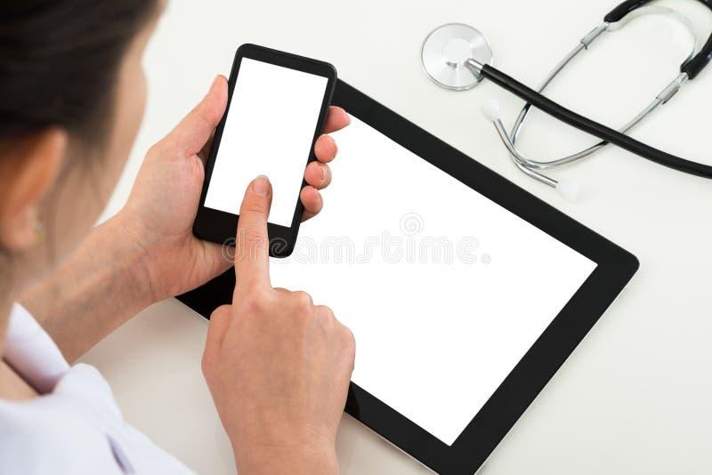 Docteur avec le téléphone portable d'affichage neutre et le comprimé numérique photo stock