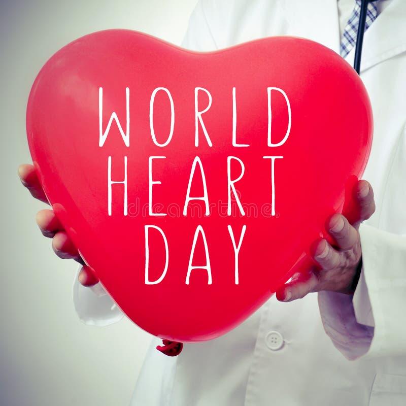 Docteur avec un ballon en forme de coeur avec le jour de coeur du monde des textes image stock