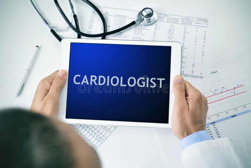 Docteur avec un comprimé avec le cardiologue de mot photo libre de droits