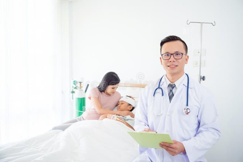 Docteur beau souriant avec le patient et la famille à l'arrière-plan image stock