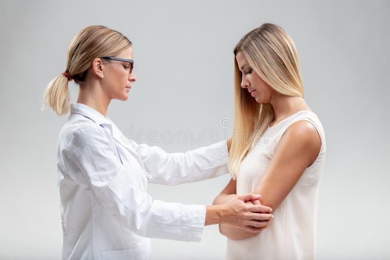 Docteur bien disposé soulageant un patient féminin photos stock