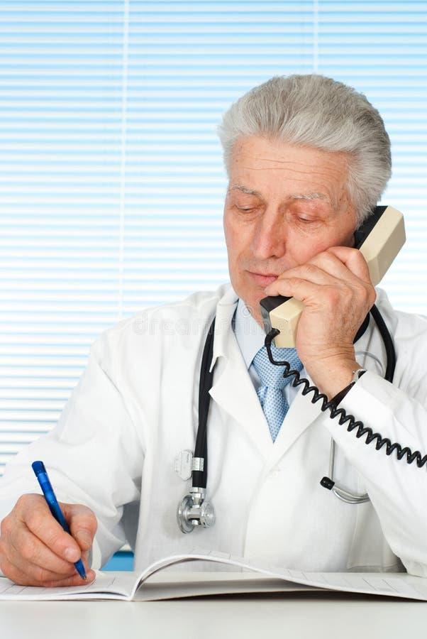 Docteur caucasien heureux avec une séance de téléphone photographie stock libre de droits