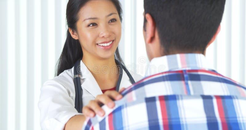Docteur chinois disant à patient les bonnes actualités photo libre de droits