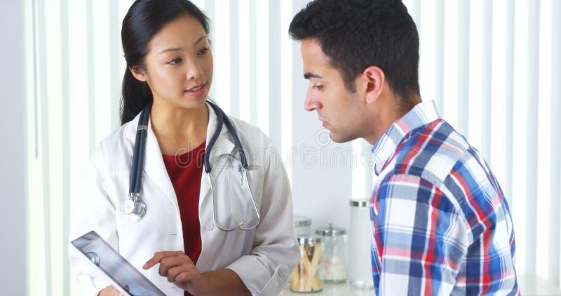 Docteur chinois expliquant le rayon X de cou au patient photographie stock libre de droits