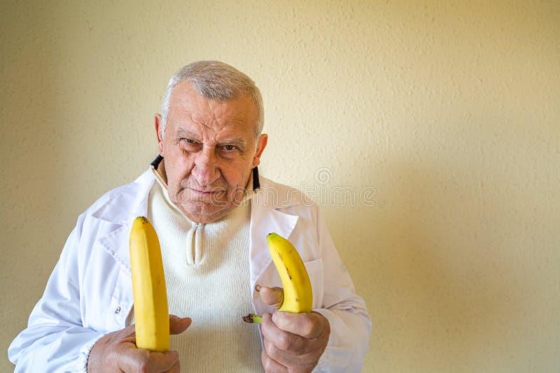 Docteur comparant des bananes comme concept photo stock