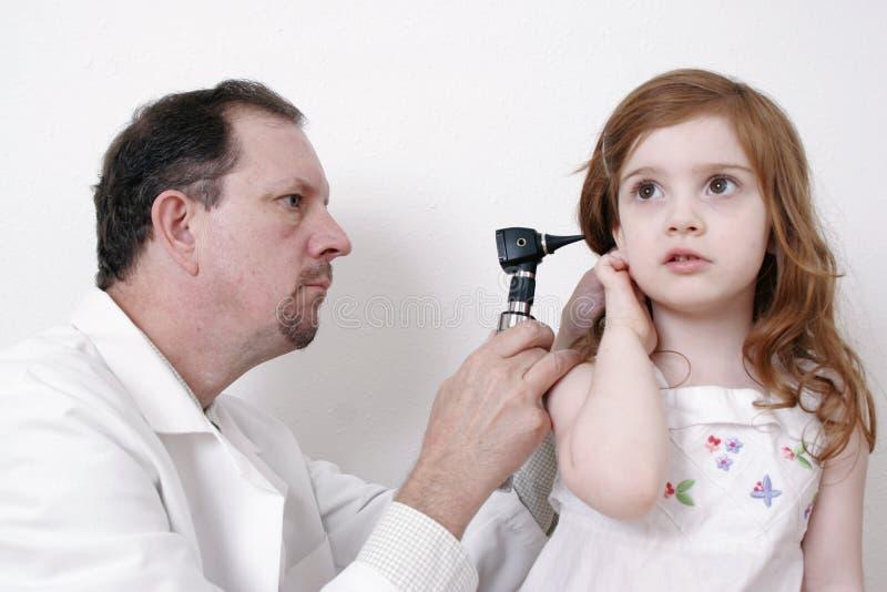 Docteur contrôlant l'oreille de petite fille photographie stock
