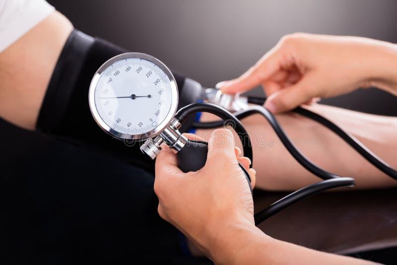 Docteur contrôlant la tension artérielle du patient photographie stock