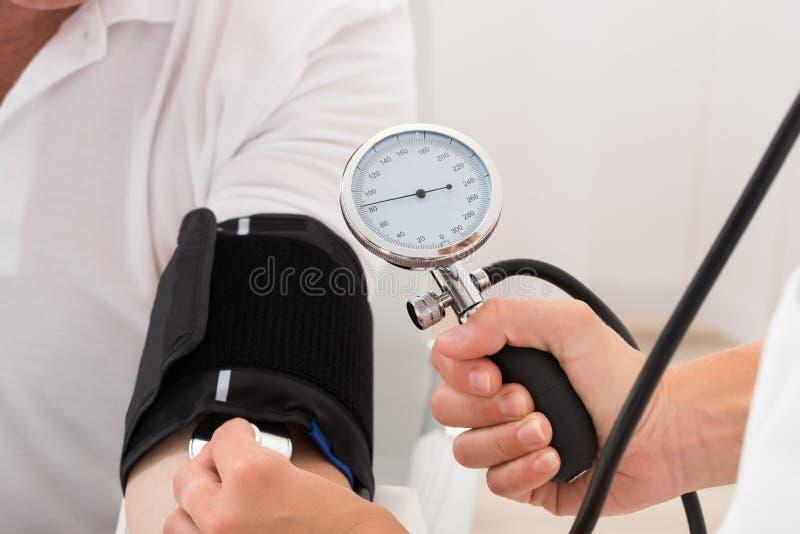 Docteur contrôlant la tension artérielle du patient images libres de droits