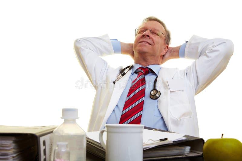 Docteur détendant à son bureau photographie stock libre de droits