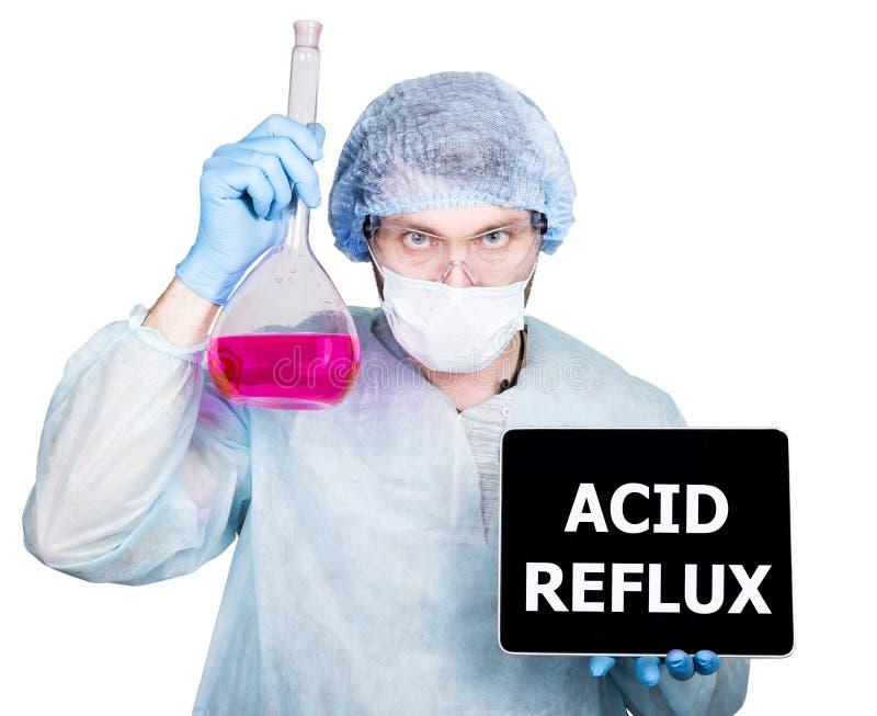 Docteur dans l'uniforme chirurgical, tenant le flacon et le PC numérique de comprimé avec le signe acide de reflux technologie, I photographie stock