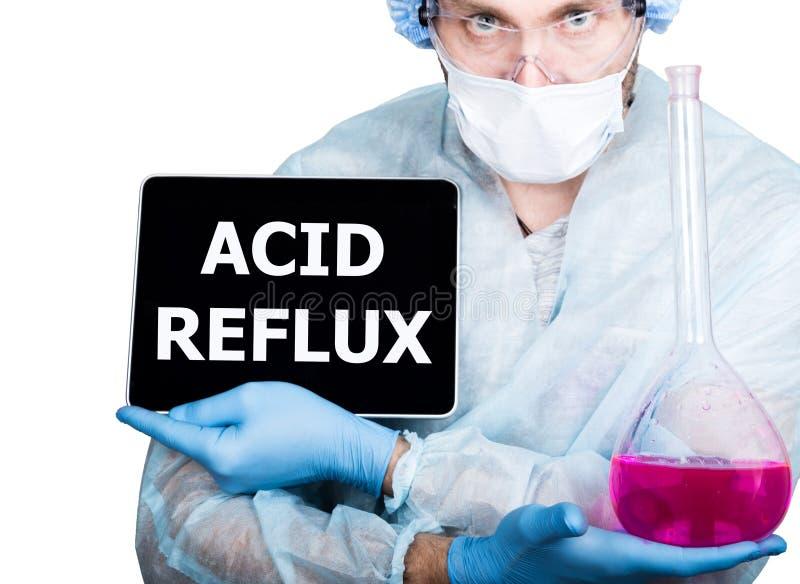 Docteur dans l'uniforme chirurgical, tenant le flacon rose et le PC numérique de comprimé avec le signe acide de reflux technolog image libre de droits