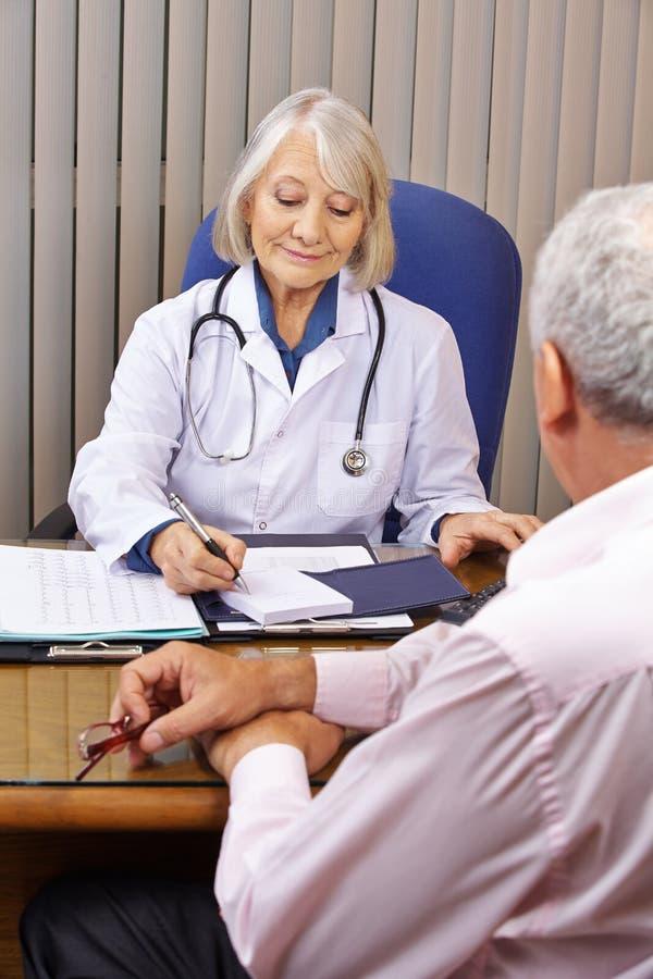 Docteur dans le bureau donnant la consultation photos stock