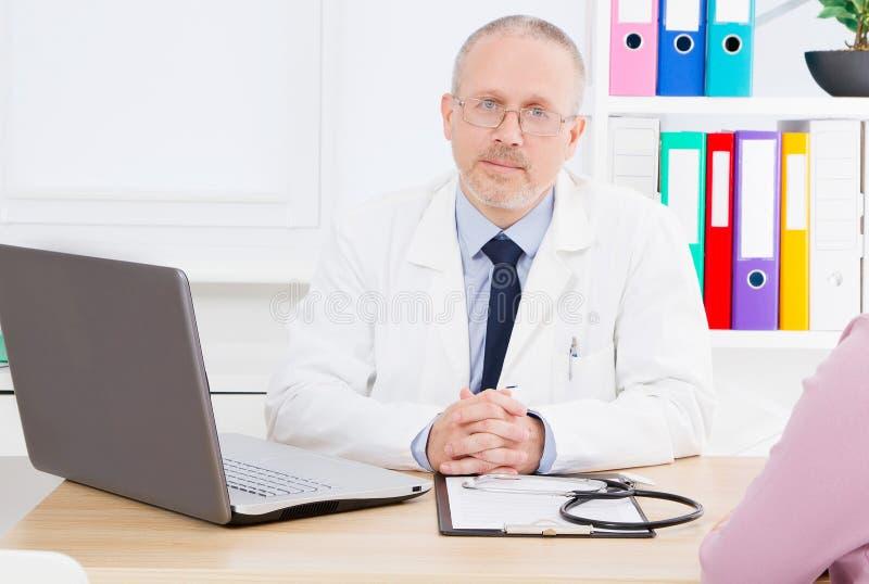 Docteur dans le bureau médical avec le patient, le Dr. dans le costume blanc de médecine, assurance-maladie, hôpital de clinique  image libre de droits