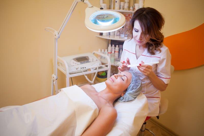 Docteur de cosmétologie mettant une femme sur la crème de visage photos libres de droits